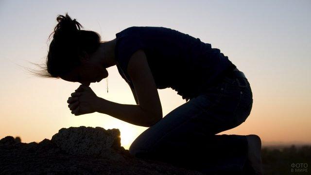 Силуэт коленопроеклонённой молящейся девушки на фоне заката