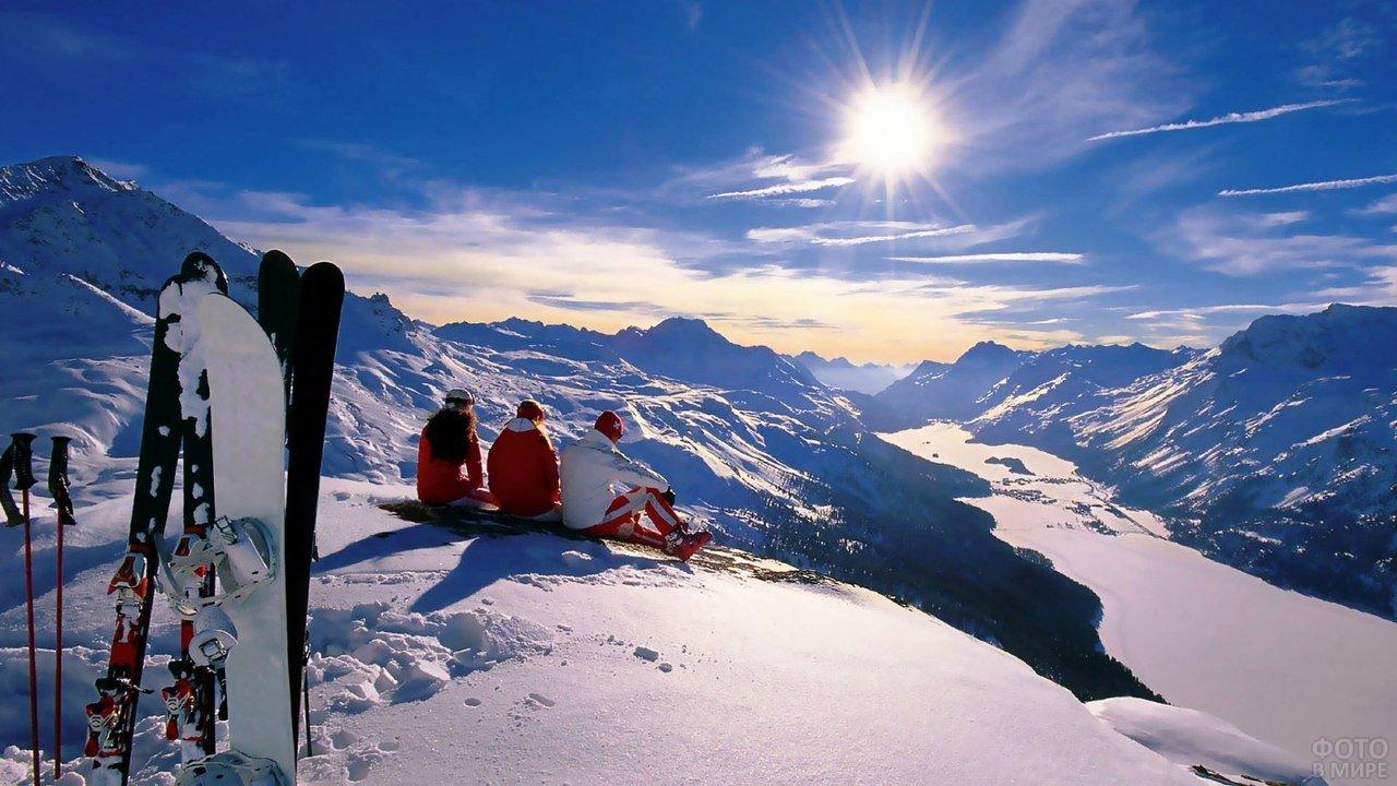 Лыжники и сноубордист отдыхают на снежном склоне Эльбруса