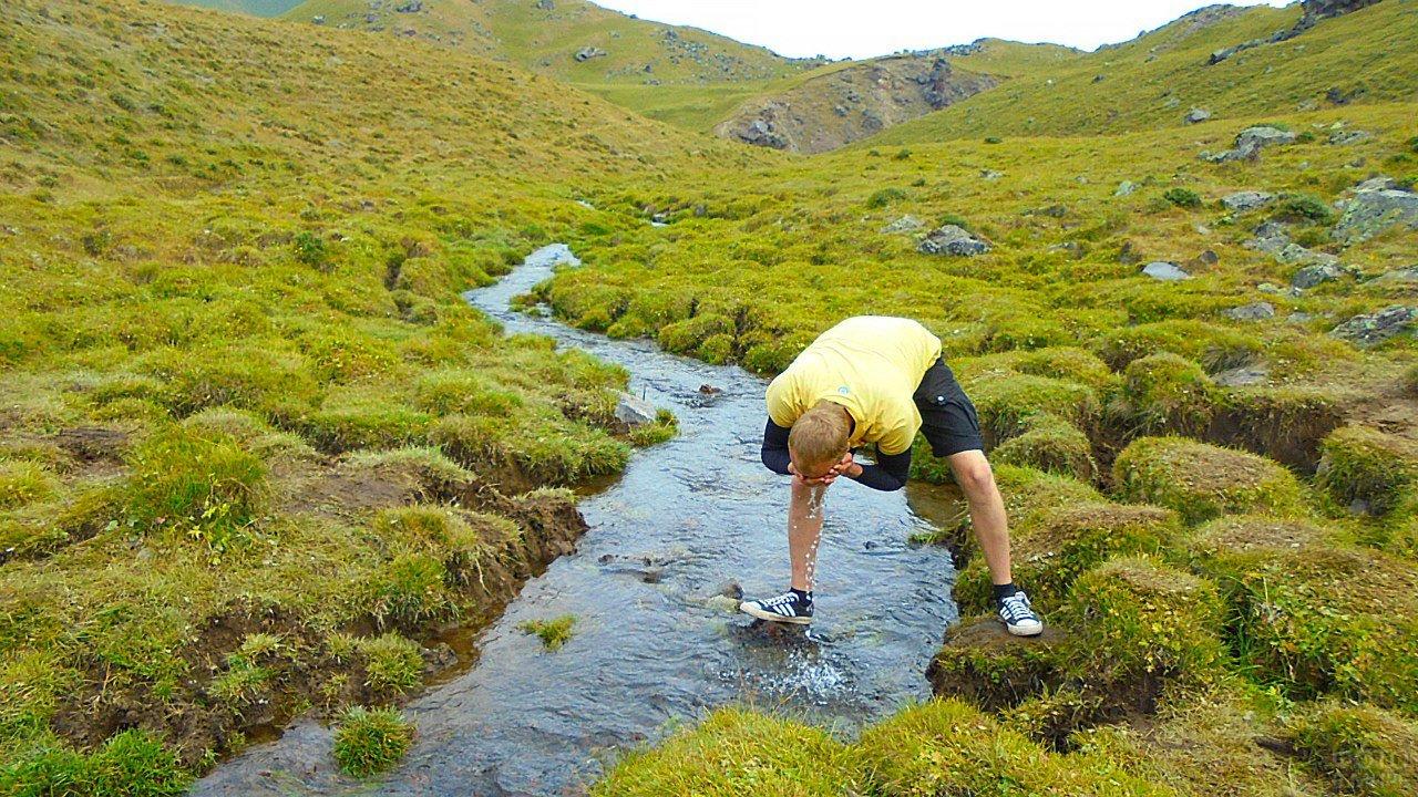 Турист умывается в горной речке у подножья Эльбруса