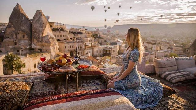 Девушка сидит за столиком на крыше на фоне города и воздушных шаров