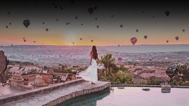 Девушка в белом платье на фоне долины с поднимающимися воздушными шарами
