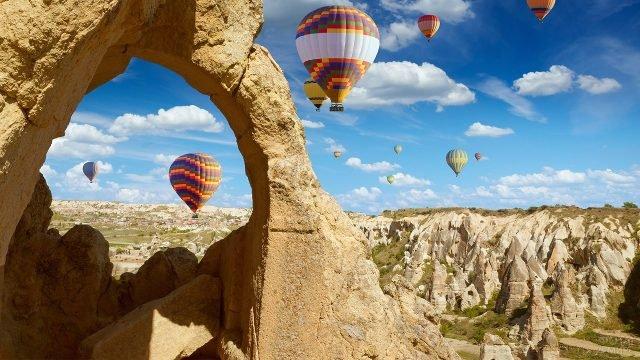 Фото воздушных шаров над долиной через скалу