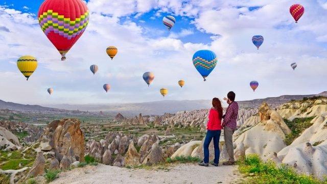 Мужчина и женщина стоят на фоне долины любви и смотрят на воздушные шары