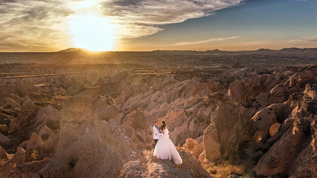Жених с невестой на фоне долины в солнечных лучах