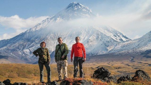 Трое туристов на Камчатке на фоне горы