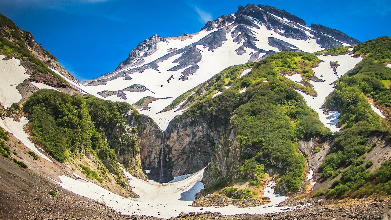 Зелёные холмы и заснеженная гора с небольшим водопадом