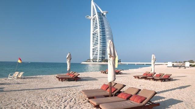 Чистый пляж с шезлонгами рядом с небоскрёбом