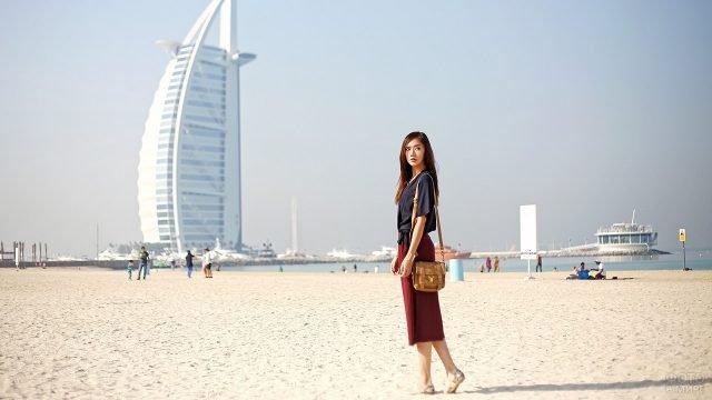 Девушка на пляже с видом на отель