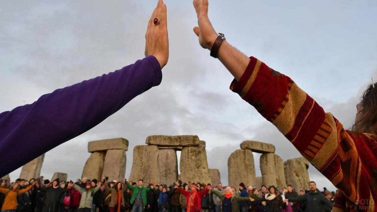 Две руки соприкосаются на фоне ритуального хоровода