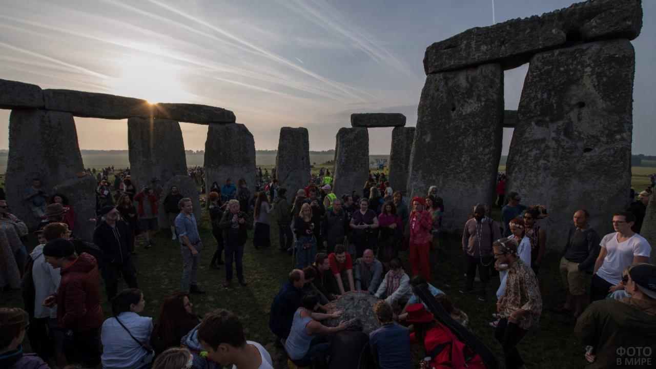 Люди прикладывают руки к ритуальному камню