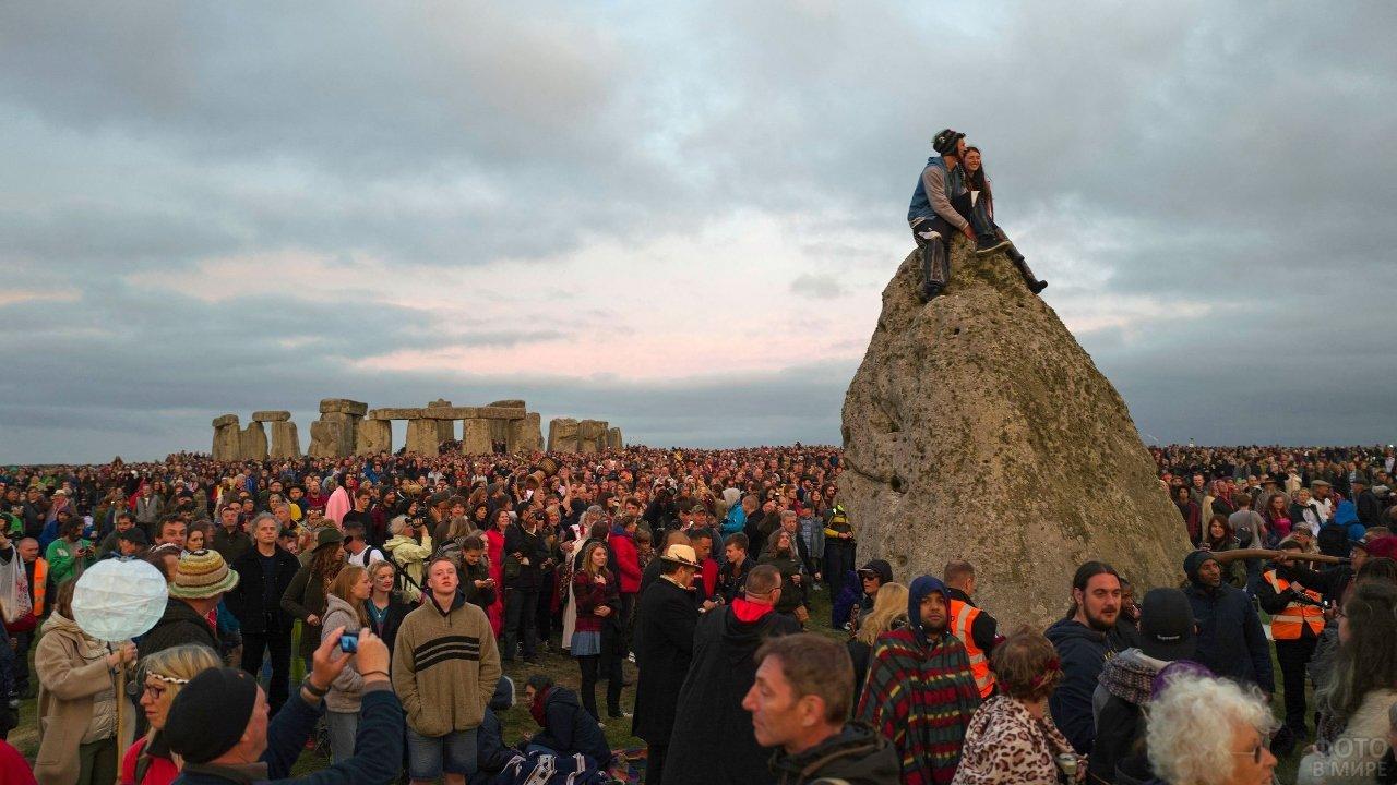 Пара сидит на камне на фоне толпы
