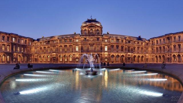 Фонтан на фоне дворца Лувра в огнях вечерней иллюминации