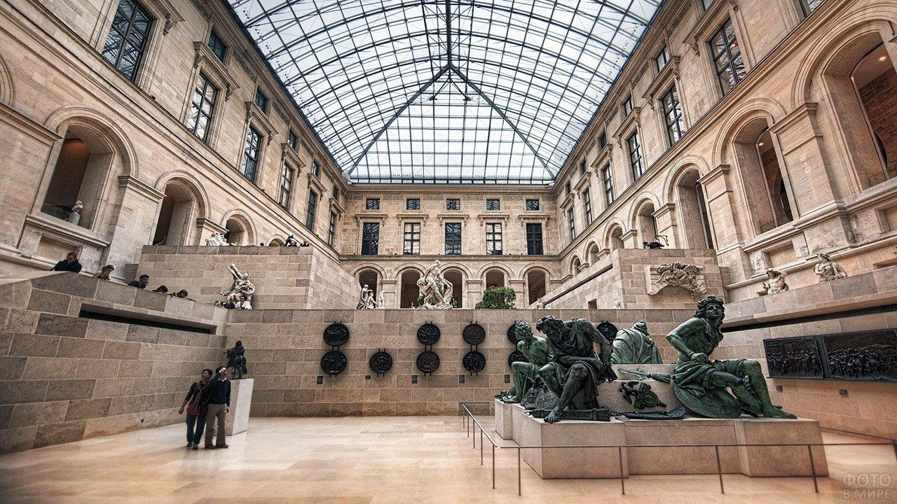 Крошечные фигурки туристов среди статуй Лувра