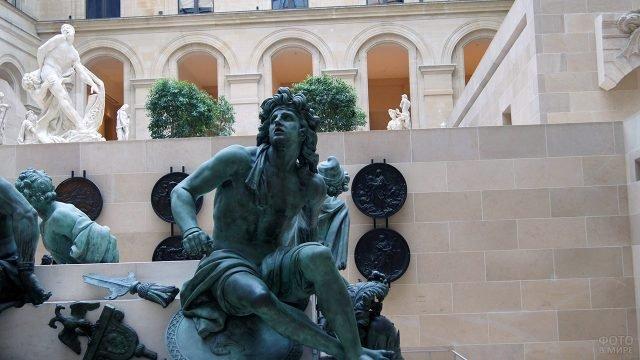Медные статуи среди мрамора в крыле Пьюджет-Корт в Лувре