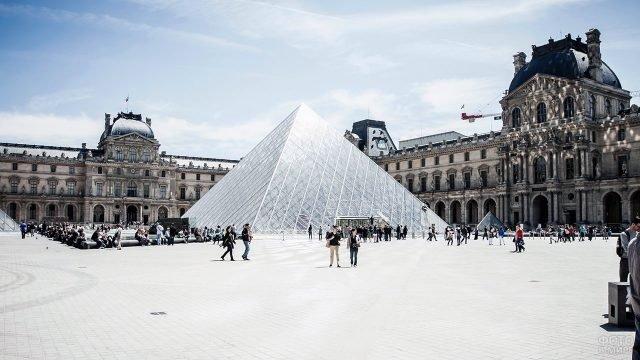 Ослепительно-яркий солнечный день в центре Парижа у стеклянной пирамиды Лувра