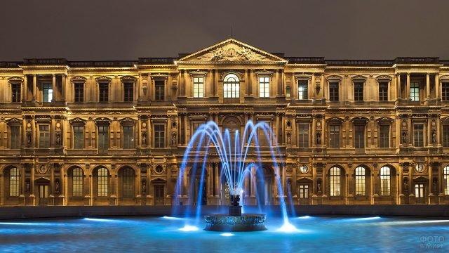 Подсвеченнные струи фонтана на фоне Луврского дворца