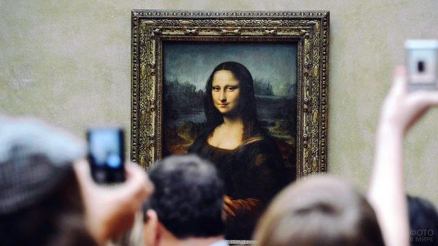 Туристы на экскурсии в Лувре фотографируют знаменитый портрет Джоконды Леонардо да Винчи