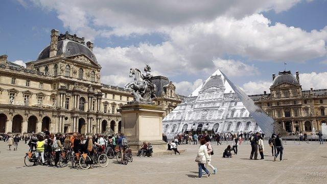 Туристы смотрят на работу французского фотографа на поверхности пирамиды Лувра