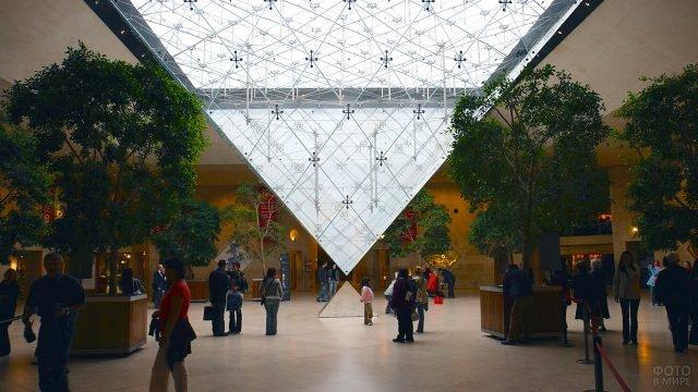 Туристы в зале под стеклянной пирамидой Лувра