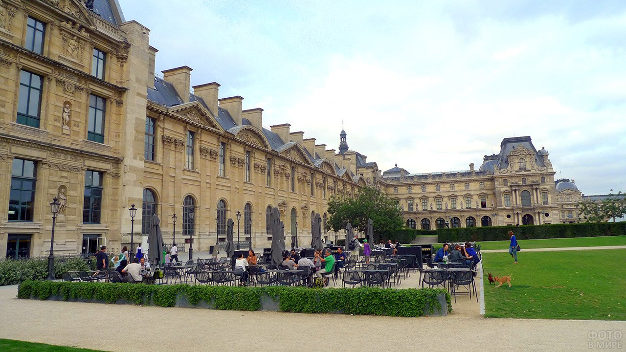 Туристы за столиками кафе во дворе Луврского дворца