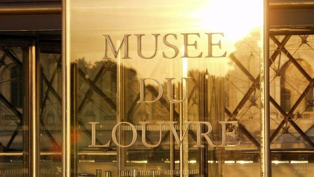 Золотая табличка на входе в музей Лувра