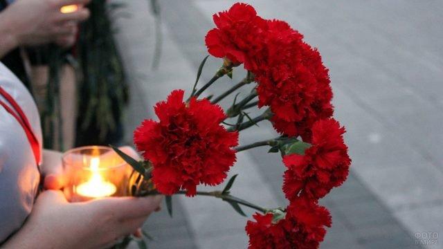 Цветы и свечи в руках участницы акции Свеча памяти 22 июня в Ростове