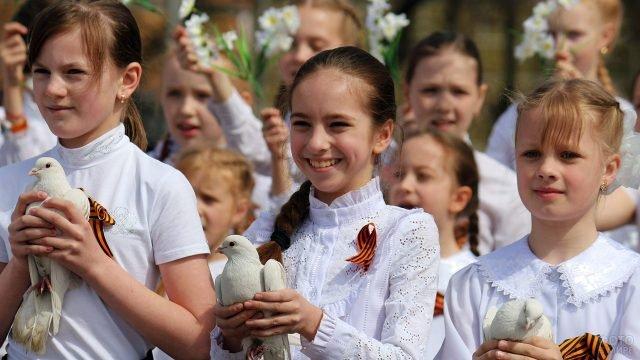 Школьницы с георгиевскими лентами и белыми голубями - символами мира - в руках