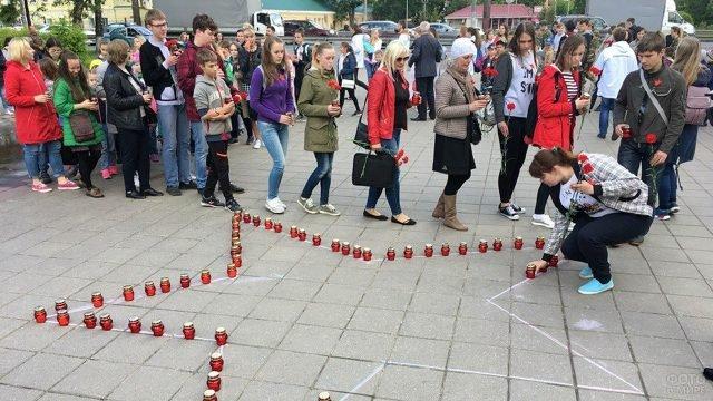 Участники акции Свеча памяти выстраивают звезду на площади города