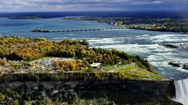 Осенний парк со смотровой площадкой сбоку от водопада