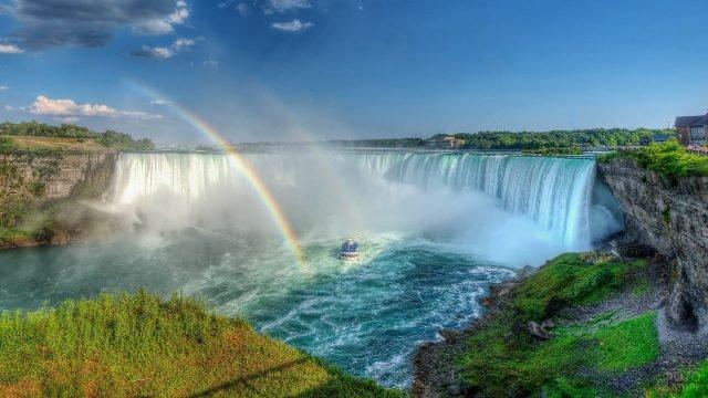 Радуга и маленький паром на фоне водопада
