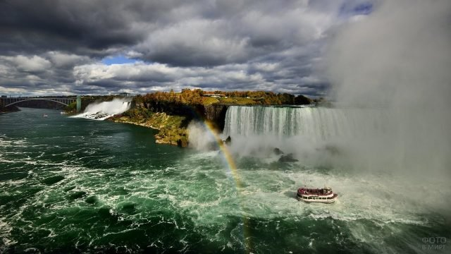 Радуга на фоне парома и двух частей водопада