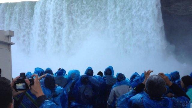 Туристы в синих дождевиках у подножья водопада