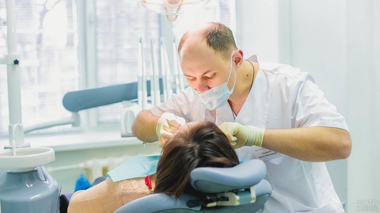 Лысеющий стоматолог за работой