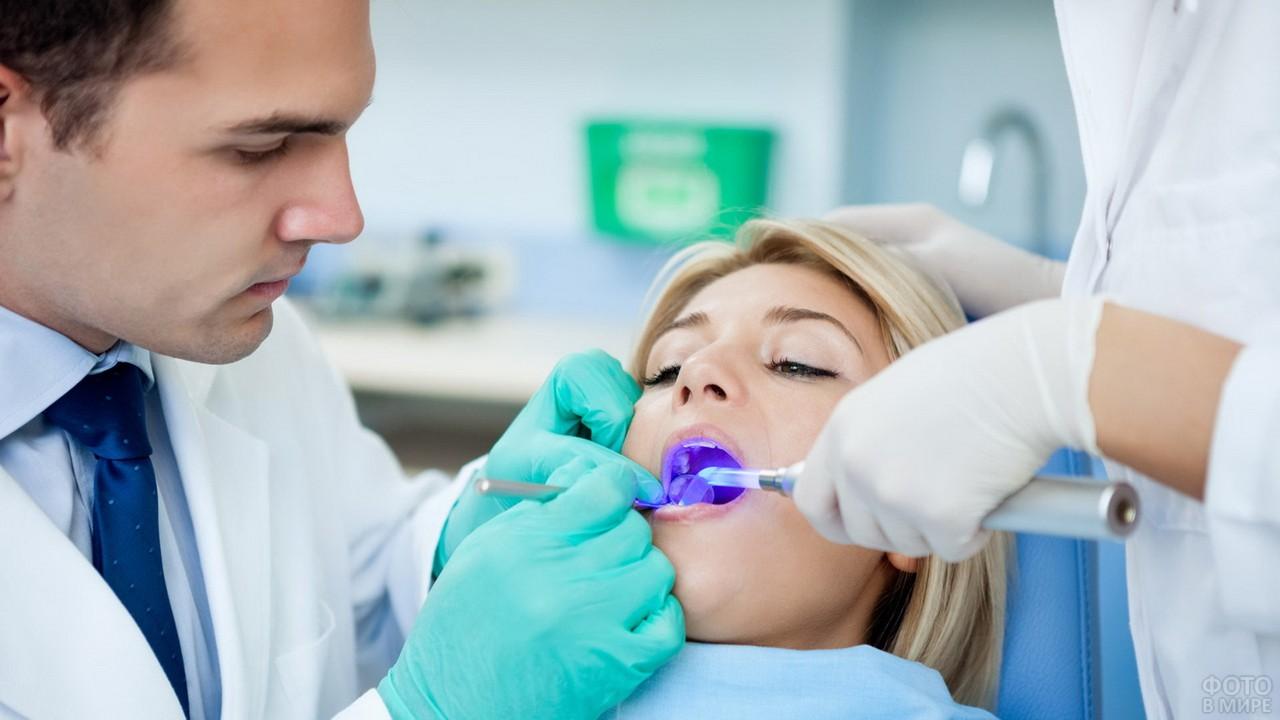 Пациентке подсвечивают рот ультрафиолетом