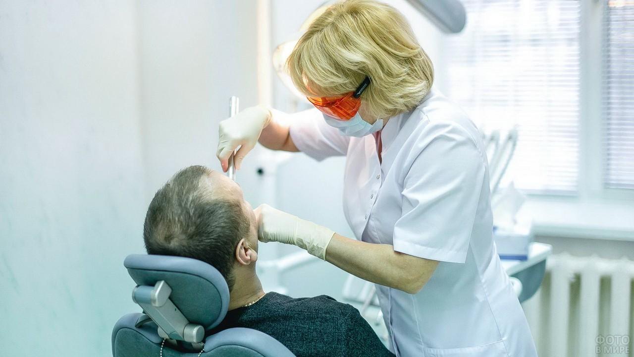 Зубной врач в оранжевых очках