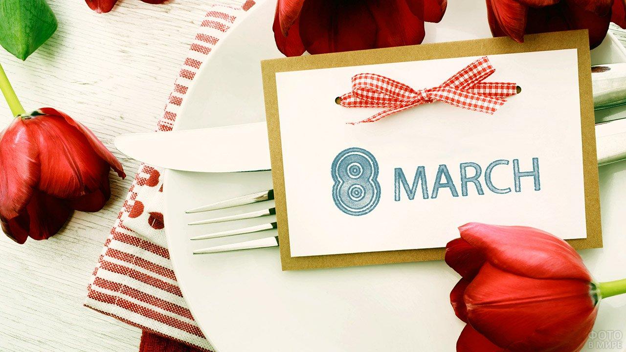 Карточка с бантиком к 8 марта на тарелке среди красных тюльпанов