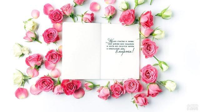 Развёрнутая открытка с поздравлением к 8 марта среди роз на белом фоне