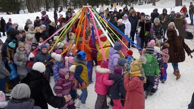 Малыши играют в карусель в Прощёное воскресенье в Подмосковье