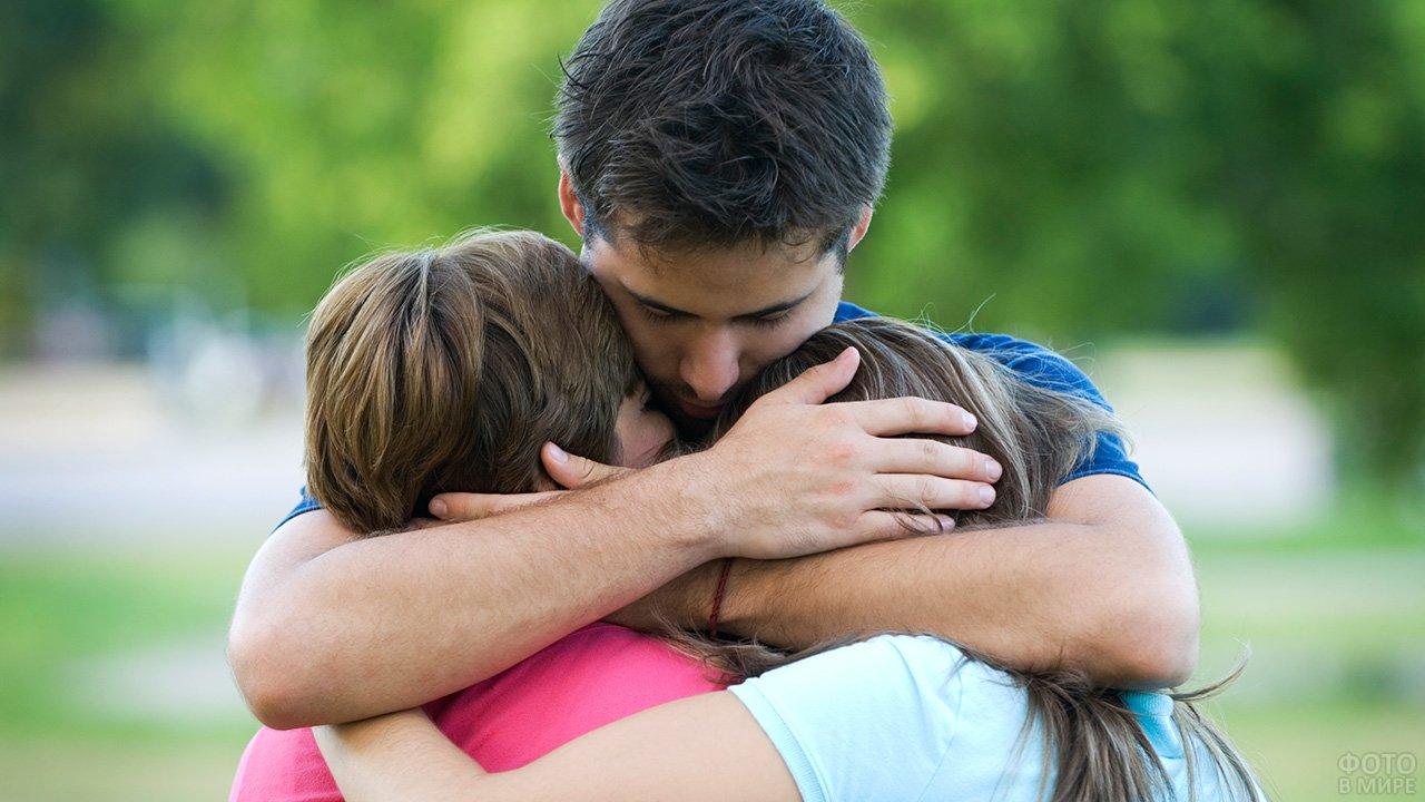 Мужчина обнимает жену и дочь прося прощения