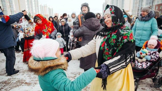 Пенсионерка и маленькая девочка танцуют в Прощёное воскресенье