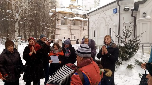 Прихожане поют в Прощёное воскресенье во дворе храма