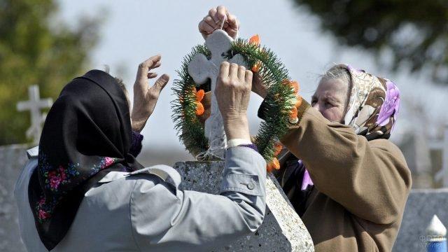 Старушки поправляют венок на могилке в Прощёное воскресенье