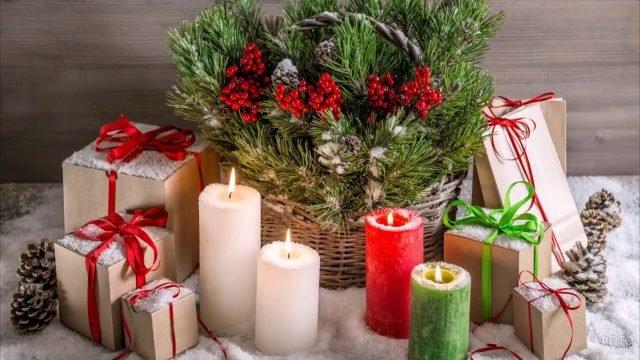 Свечи, подарки и корзина с еловыми ветками на рождество