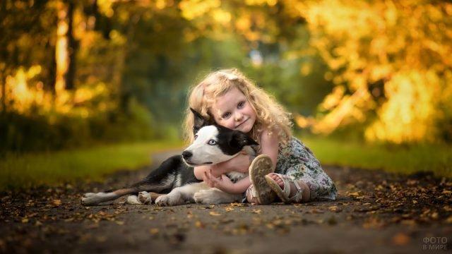Девочка обнимает чёрно-белого пса