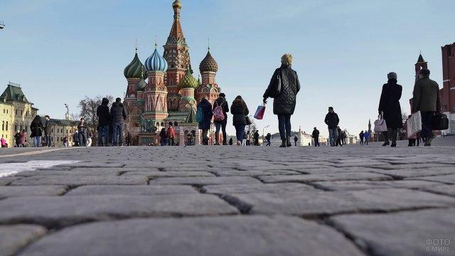 Люди идут по брусчатке Красной площади в сторону храма Василия Блаженного