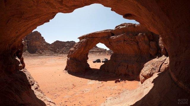 Джипы между каменных арок в Сахаре