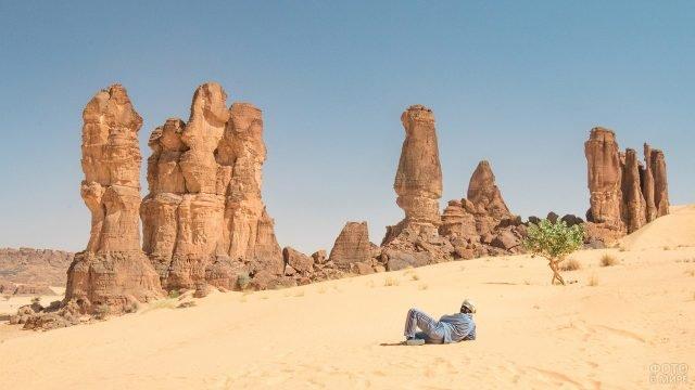 Отдыхающий африканец на песке плато Эннеди в Сахаре