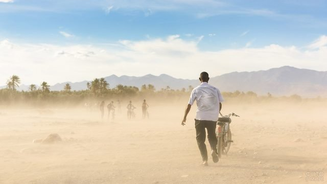 Туристы с велосипедами бегут в оазис Скоура укрыться от песчаной бури в Сахаре