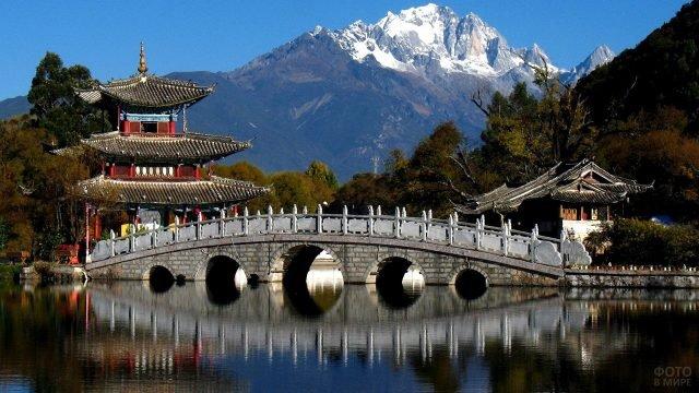 Горбатый мостик у монастыря на фоне Тибетских гор