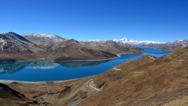 Горный пейзаж с автотрассой вдоль реки в Тибете
